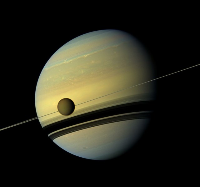 A giant of a moon appears before a giant of a planet undergoing seasonal changes in this natural color view of Titan and Saturn from NASA's Cassini spacecraft. Titan, Saturn's largest moon, measures 3,200 miles across and is larger than the planet Mercury. As the seasons have changed in the Saturnian system, and spring has come to the north and autumn to the south, the azure blue in the northern Saturnian hemisphere that greeted Cassini upon its arrival in 2004 is now fading. The southern hemisphere, in its approach to winter, is taking on a bluish hue. This mosaic combines six images — two each of red, green and blue spectral filters — to create this natural color view. The images were obtained with the Cassini spacecraft wide-angle camera on May 6, 2012, at a distance of approximately 483,000 miles from Titan.