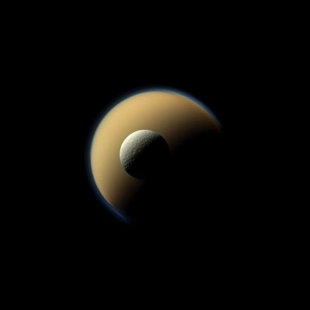 Saturn's largest and second largest moons, Titan and Rhea, appear to be stacked on top of each other in this true-color scene from NASA's Cassini spacecraft. The north polar hood can be seen on Titan (3,200 miles across) appearing as a detached layer at the top of the moon on the top right. Images taken using red, green and blue spectral filters were combined to create this natural-color view. The images were acquired with the Cassini spacecraft narrow-angle camera on June 16, 2011, at a distance of approximately 1.1 million miles.