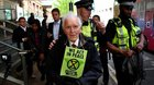 An 83 year old climate change protester being arrested in London today after he climbed on top of a DLR train.