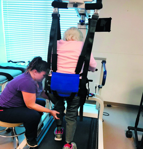 An 82-year-old female who suffered a left corona radiata CVA  and presented with decreased left-sided neuromuscular control and coordination uses the body weight support device over the treadmill. The therapist assists with advancement and placement of her left lower extremity during functional ambulation.