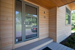 Front Door - recessed entrance with stained cypress siding at walls and nautral cypress siding at underside of porch roof and soffits.