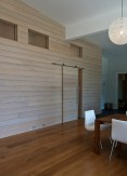 Cypress interior wall with transoms above to allow light into the core of home