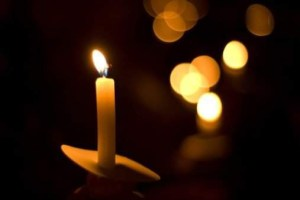 photo of a yellow candle against a dark background with sevreal blurry candle lights in the background