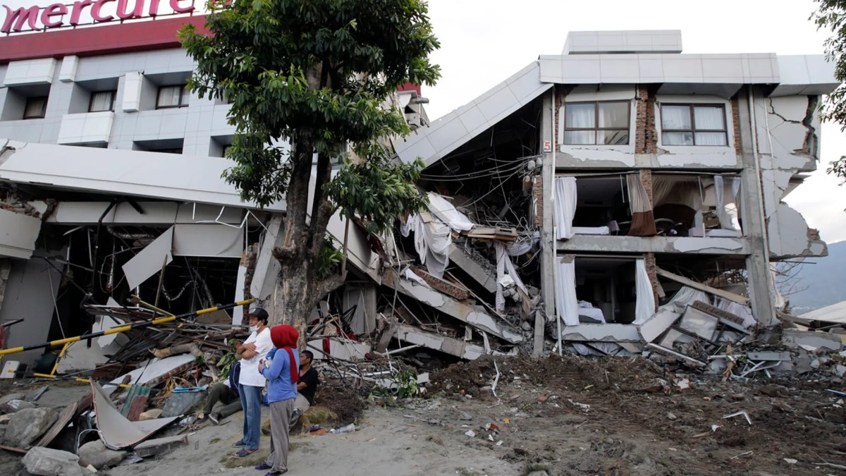 Filipinos stand beside the heavily damaged Mercure hotel after a massive earthquake and tsunami hit Palu, Central Sulawesi, Indonesia Thursday, Oct. 4, 2018. (AP Photo/Aaron Favila)