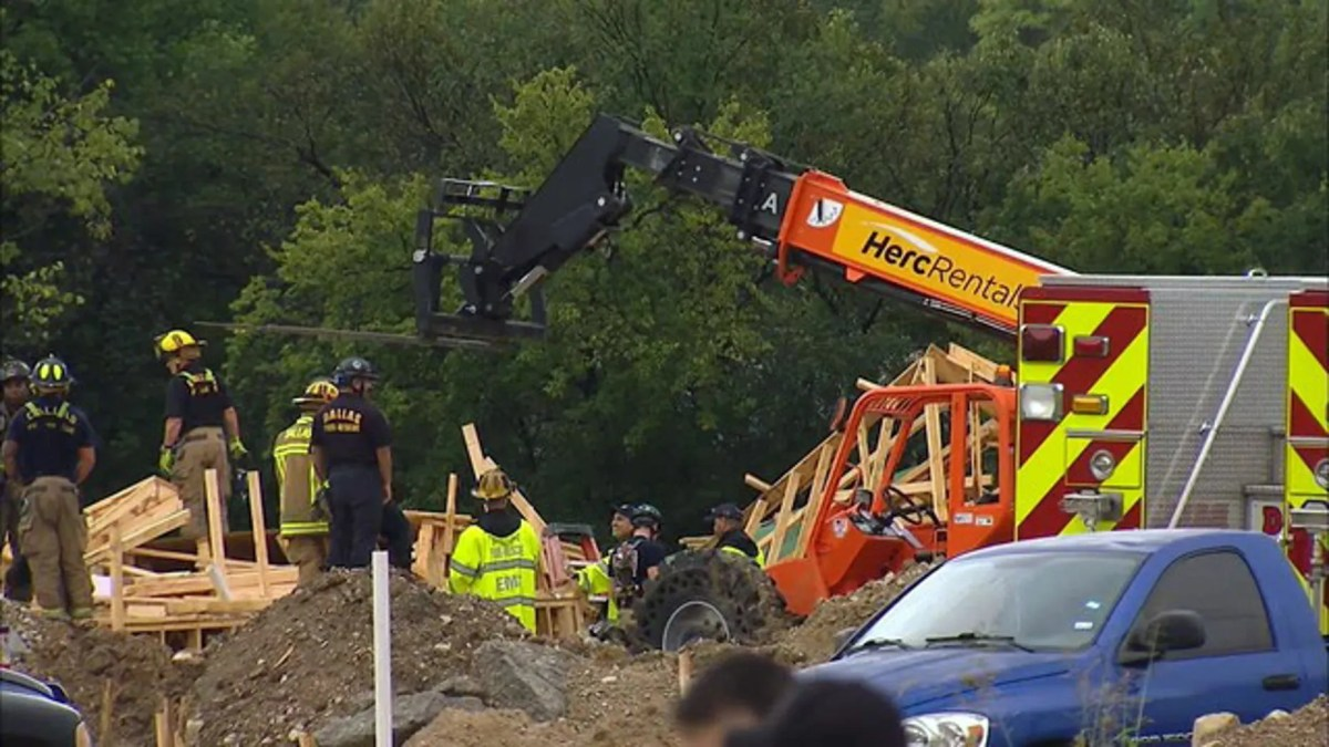 Rescue personnel examining the scene where a townhouse under construction collapsed in West Dallas.