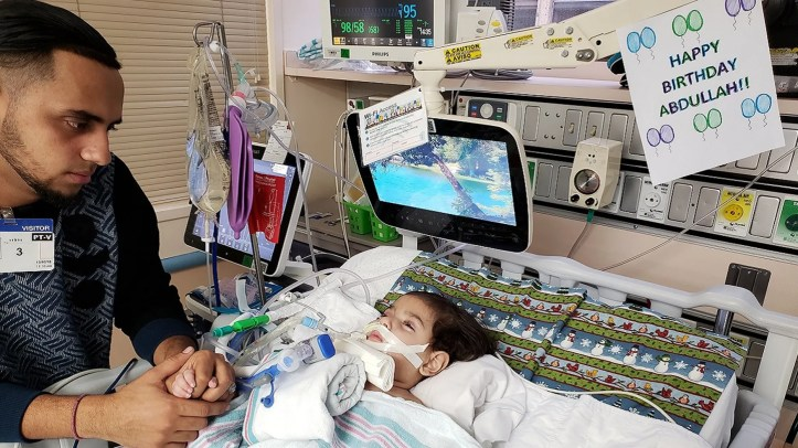 Ali Hassan, 22, sits with his son Abdullah, 2, who is on life support at UCSF Benioff Children's Hospital in Oakland, Calif.