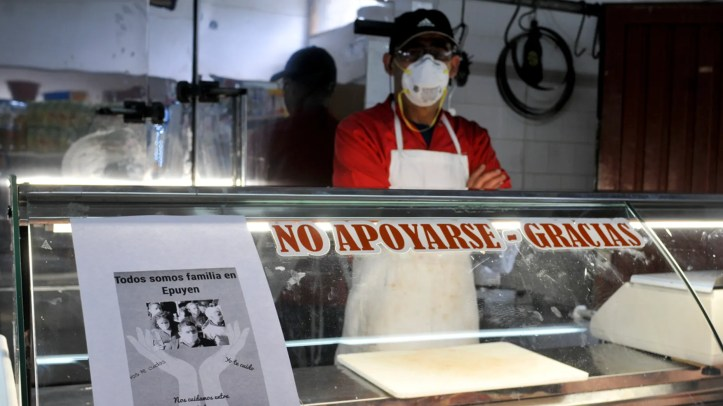 A man wearing a mask waits for clients at his shop, with a sign posted that reads in Spanish
