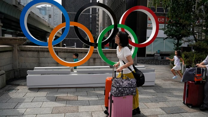 FILE - In this Aug. 19, 2019, file photo, tourists walk with their luggage past the Olympic rings in Tokyo. Frustrated residents of Japan got another shot at attending next year's Tokyo Olympics when organizers on Friday, Nov. 8, 2019, put about 1 million more tickets into the latest lottery. (AP Photo/Jae C. Hong, File)