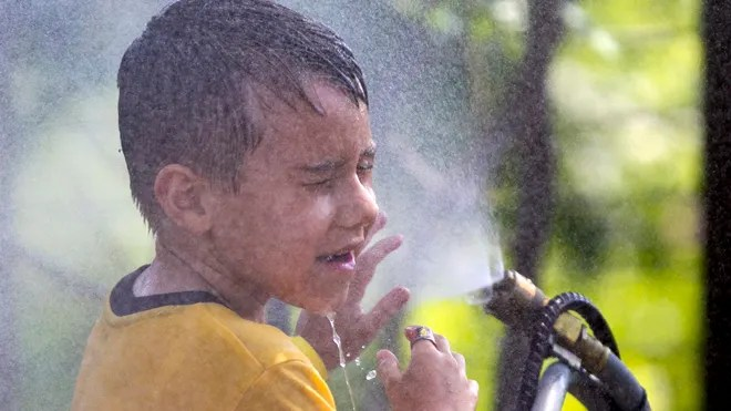 July 6, 2012: Six-year-old Alexander Merrill of Sioux Falls, S.D., cools off in a cloud of mist at the Henry Doorly Zoo in Omaha, Neb., as temperatures reached triple digits. (AP Photo/Nati Harnik)