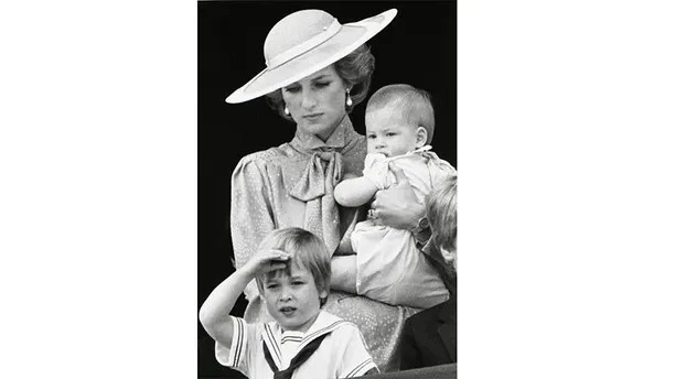 Prince William makes a royal salute as he watches the scene of Trooping the Colour from the balcony of Buckingham Palace with his brother Harry and mother Princess Diana on June 15, 1985 in London. REUTERS/Roy Letkey - GF2DUBHQSTAF