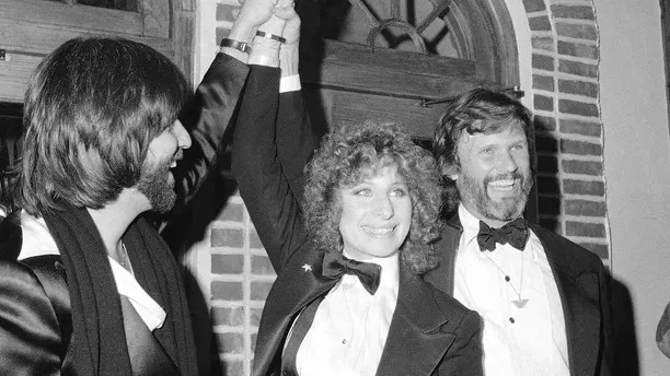 "FILE - In this Dec. 23, 1976 file photo, producer Jon Peters, from left, Barbra Streisand and Kris Kristofferson appear at a  preview of the film, ""A Star is Born,"" in New York. Streisand is giving an early thumbs-up to the remake of ""A Star Is Born"" with Lady Gaga and Bradley Cooper. Streisand and Kristofferson topped the 1976 version of the romantic drama about a rising performer and a fading star.  (AP Photo/Suzanne Vlamis, File)"