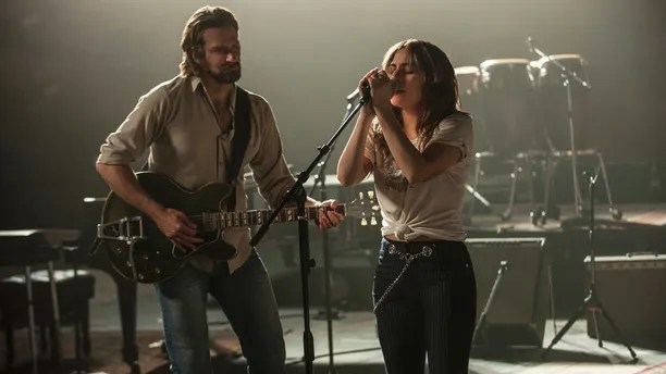 "This image released by Warner Bros. shows Bradley Cooper, left, and Lady Gaga in a scene from the latest reboot of the film, ""A Star is Born."" Barbra Streisand is giving an early thumbs-up to the remake of ""A Star Is Born"" with Lady Gaga and Bradley Cooper. Streisand and Kris Kristofferson topped the 1976 version of the romantic drama about a rising performer and a fading star. (Neal Preston/Warner Bros. via AP)"