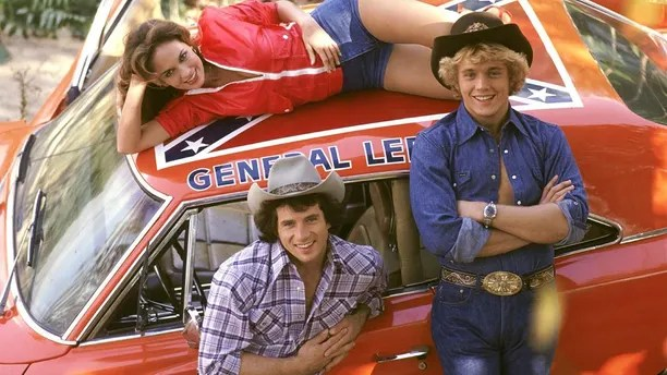 """John Schneider (right) with his """"Dukes of Hazzard"""" co-stars Tom Wopat and Catherine Bach."""