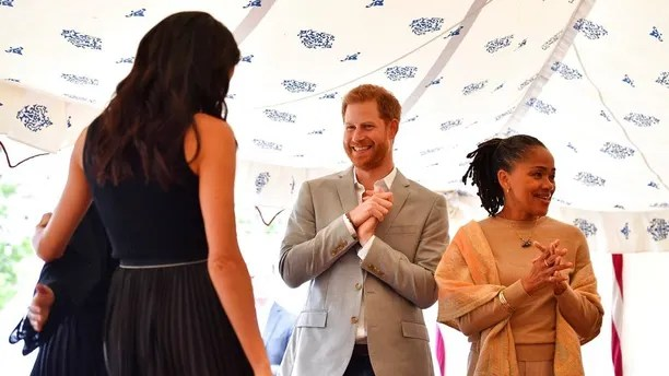 Britain's Prince Harry and Doria Ragland, gesture as Meghan, the Duchess of Sussex, left, hugs a woman involved with the cookbook