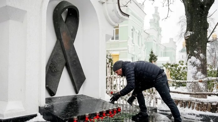 A participant lays flowers as he takes part in a ceremony to mark World AIDS Day in Kiev, Ukraine, Dec. 1, 2016.