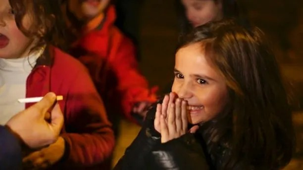 Ines, 8 years old, reacts as her father Frederico hands her her first cigarette, in the village of Vale de Salgueiro, northern Portugal, during the local Kings' Feast Friday, Jan. 5, 2018. The village's Epiphany celebrations, called Kings' Feast, feature a tradition that each year causes an outcry among outsiders: parents encourage their children, some as young as 5, to smoke cigarettes. Parents buy the packs of cigarettes for their children. Locals say the practice is centuries-old, but nobody is sure what it symbolizes nor why the children are incited to smoke. (AP Photo/Armando Franca)