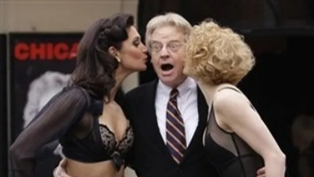 US television presenter Jerry Springer receives a kiss from Chicago Showgirls as it is announced he will make his stage debut on June 1, 2009, guest starring as Billy Flynn in the West End musical Chicago, at the Cambridge Theatre in central London, Tuesday, Feb. 17, 2009. (AP Photo/Joel Ryan)