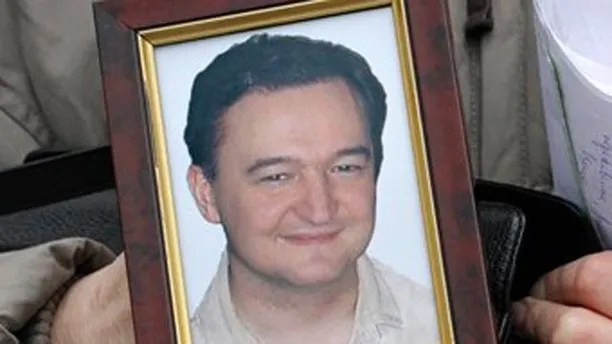 This is a  Monday, Nov. 30, 2009 file photo showing a portrait of lawyer Sergei Magnitsky who died in jail, as it is held  by his mother Nataliya Magnitskaya,  as she speaks during an exclusive interview with the AP in Moscow, Russia, Monday, Nov. 30, 2009.