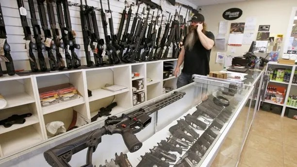 "An AR-15 sits on a display case as Willy Ludlow, owner of  the ""Ready Gunner"" gun store, talks on the phone in Provo, Utah, U.S., June 21, 2016. REUTERS/George Frey - RTX2HHFE"