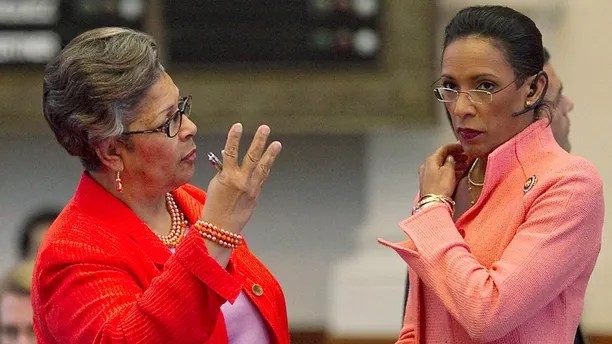 FILE - In this Thursday, May 26, 2011 file photo, Rep. Dawnna Dukes, right, listens to Rep Senfronia Thompson on the House floor during session in Austin, Texas. Travis County prosecutors say in a court filing that state Rep. Dukes spent more than $51,000 on an online psychic, appeared for work at the Capitol impaired and hid a cellphone from investigators. (Ralph Barrera/ Austin American-Statesman via AP)/Austin American-Statesman via AP, File)
