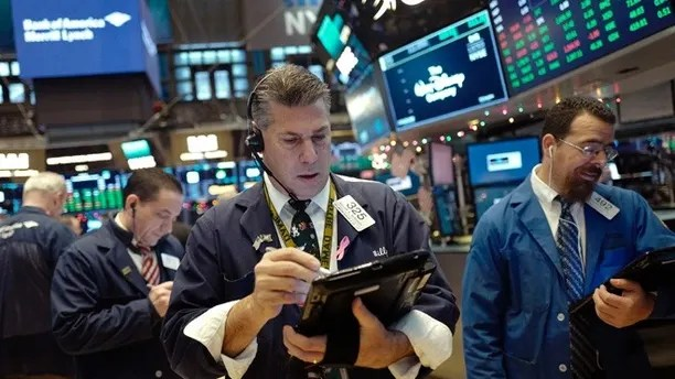 Trader William McInerney works at the New York Stock Exchange, Tuesday, Dec. 19, 2017. (AP Photo/Mark Lennihan)