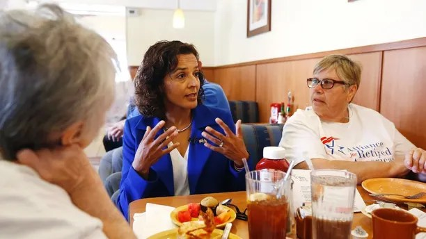 In this April 10, 2018, photo, Democratic candidate for the Arizona 8th Congressional District special election Dr. Hiral Tipirneni, center, talks with supporters at a local restaurant in Sun City, Ariz. Tipirneni is running against former Arizona Republican state Sen. Debbie Lesko in a special election to fill the seat vacated by Republican Rep. Trent Franks. (AP Photo/Ross D. Franklin)