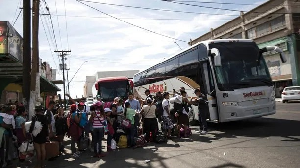Migrants in a caravan of Central American asylum-seekers board buses in Mexicali, Mexico, Thursday, April 26, 2018, for a two-hour drive to Tijuana to join up with about 175 others who already arrived. Lawyers planned free workshops on the U.S. immigration system on Friday and Saturday as many planned to seek asylum starting Sunday at San Diego's San Ysidro border crossing, the nation's busiest. (AP Photo/Hans-Maximo Musielik)