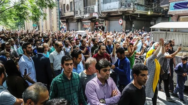A group of protesters chant slogans at the old grand bazaar in Tehran, Iran, Monday, June 25, 2018. Protesters in the Iranian capital swarmed its historic Grand Bazaar on Monday, news agencies reported, and forced shopkeepers to close their stalls in apparent anger over the Islamic Republic's troubled economy, months after similar demonstrations rocked the country. (Iranian Labor News Agency via AP)