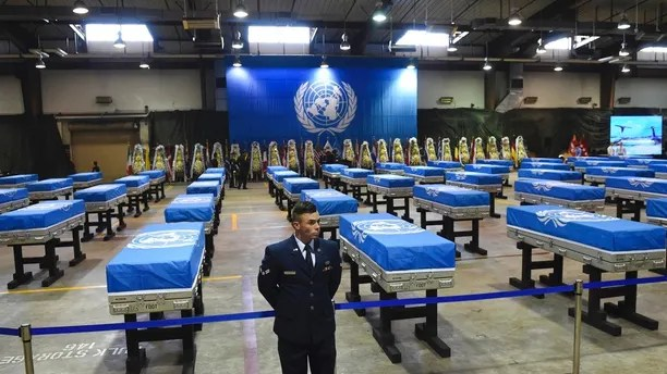 A U.S. airman stands guard next to caskets containing remains of U.S. soldiers killed in the Korean War and collected in North Korea before a repatriation ceremony at Osan Air Base in Pyeongtaek, South Korea, on Wednesday, Aug. 1, 2018. North Korea handed over 55 boxes of the remains last week as part of agreements reached during a historic June summit between its leader Kim Jong Un and U.S. President Donald Trump. (Jung Yeon-je/Pool Photo via AP)