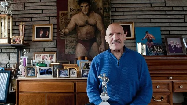 """FILE - In this March 27, 2013, file photo, Bruno Sammartino sits in front of pictures, panitings and trophies highlighting his storied career as a wrestler and weightlifter, at his home in his North Hills, Pa., home. Bruno Sammartino, professional wrestling's """"Living Legend"""" and one of its longest-reigning champions, has died. Sammartino was 82.  Family friend and former wrestling announcer Christoper Crusie saids Sammartino died Wednesday morning, April 18, 2018, and had been hospitalized for two months. (Andrew Russell/Pittsburgh Tribune-Review via AP, File)"""