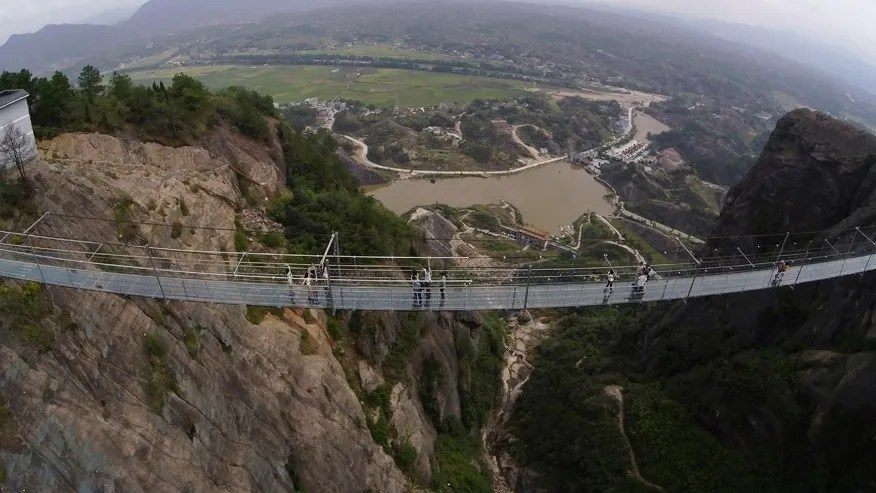 Visitors walk across a glass-bottomed suspension bridge as seen from the air in a scenic zone in Pingjiang county in southern China's Hunan province, Sept. 24, 2015.