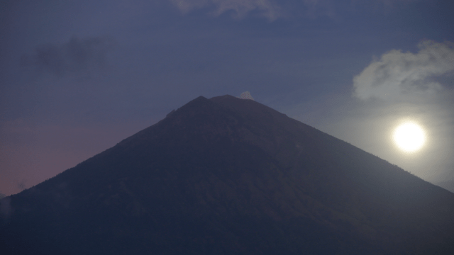 A full moon is set behind the Mount Agung volcano in Karangasem, Bali, Indonesia, Friday, Oct. 6, 2017.