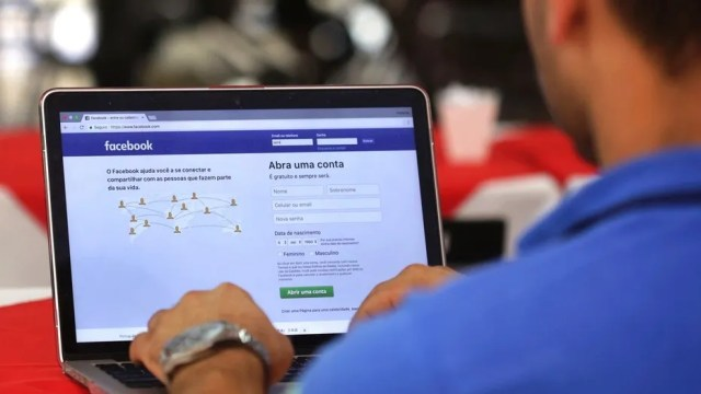 """FILE - In this Thursday, Jan. 4, 2018, file photo, a man demonstrates how he enters his Facebook page as he works on his computer at a restaurant in Brasilia, Brazil. Facebook users will soon see more local news and more posts from friends and family as the company tries to give users more """"meaningful social interactions,"""" as CEO Mark Zuckerberg said recently. (AP Photo/Eraldo Peres, File)"""