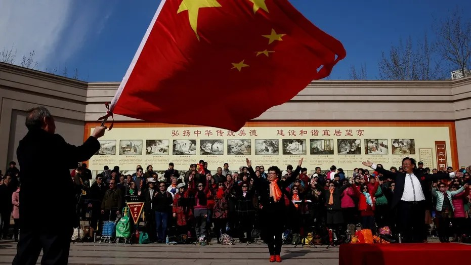 File photo: A man waves the Chinese national flag as an amateur choir performs in a park in a residential neighbourhood in Beijing, China February 28, 2017. (REUTERS/Thomas Peter)