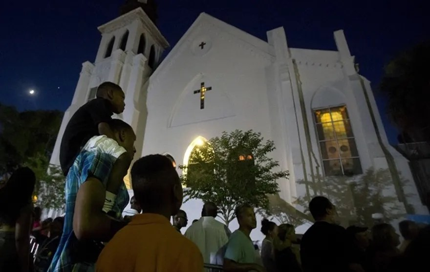 A father carries his son on his back as they listen to gospel music being sung during a vigil outside Emanuel African Methodist Episcopal Church in Charleston, June 20, 2015. The church will reopen tomorrow for its first service since Dylann Roof, a 21-year-old with a criminal record, is accused of killing nine people at a Bible-study meeting in the historic African-American church in Charleston, South Carolina, in an attack U.S. officials are investigating as a hate crime.      REUTERS/Carlo Allegri - RTX1HF6Y