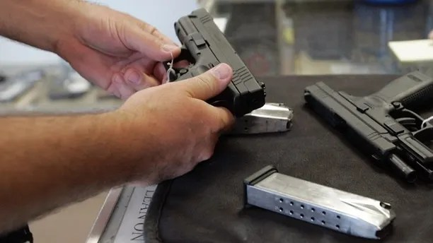 A customer inspects a 9mm handgun at Rink's Gun and Sport in the Chicago, suburb of Lockport, Illinois June 26, 2008. For the first time in U.S. history, the Supreme Court ruled on Thursday that individual Americans have the right to own guns for personal use, and struck down a strict gun control law in the U.S. capital. The landmark 5-4 ruling marked the first time in nearly 70 years the country's high court has addressed whether the Second Amendment of the U.S. Constitution protects an individual right to keep and bear arms, rather than a right tied to service in a state militia.   REUTERS/Frank Polich (UNITED STATES) - RTX7DDO