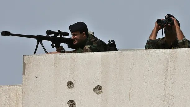 Lebanese army snipers take their positions on the top of a building, as they secure the area where the United Nations secretary-general Ban Ki-moon and other delegations suppose to visit it, in the northern city of Tripoli, Lebanon, Friday, March 25, 2016. Ban appealed Friday from Lebanon, urging the international community to provide necessary funding to help finish the rebuilding of a Palestinian refugee camp destroyed in fierce battles against al-Qaida-inspired militants almost a decade ago. (AP Photo/Hussein Malla)