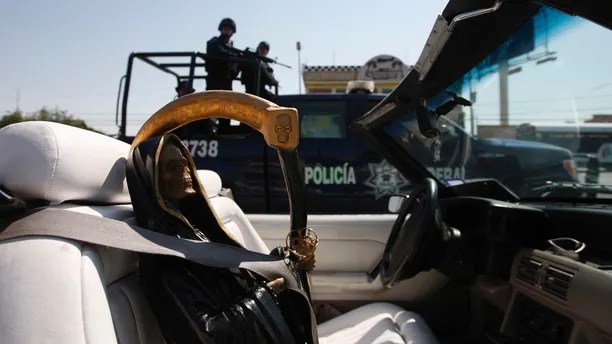 Federal police on patrol travel past a depiction of La Santa Muerte, or the Saint of Death, held in place by a seat belt in a car, during a rally in Ciudad Juarez June 19, 2011. More than 70 believers of Santa Muerte took part in the rally in Ciudad Juarez on Sunday to demand for increased security and a stop to violence in the city. REUTERS/Jose Luis Gonzalez (MEXICO - Tags: CIVIL UNREST CRIME LAW SOCIETY RELIGION IMAGES OF THE DAY) - RTR2NUUG