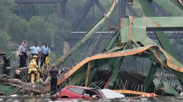 In this Aug. 1, 2007 file photo, emergency personnel work at the scene where the Interstate 35W bridge collapsed over the Mississippi River in Minneapolis. Tuesday, Aug. 1, 2017 marks the ten-year anniversary of the disaster killed 13 people and injured 145. (Jeff Wheeler/Star Tribune via AP File)
