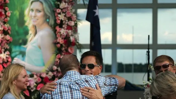 Don Damond hugs supporters and loved ones prior to a memorial service for his fiancé Justine Damond, seen in photo at left, Friday, Aug. 11, 2017, at Lake Harriet in Minneapolis. Damond was killed by a Minneapolis police officer on July 15 after she called 911 to report a possible sexual assault near her home.  (Anthony Souffle/Star Tribune via AP)