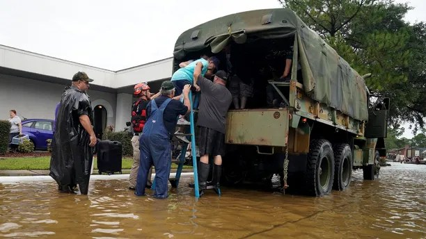 Volunteers load people into a collector's vintage military truck to evacuate them from flood waters from Hurricane Harvey in Dickinson, Texas, U.S. August 27, 2017. REUTERS/Rick Wilking - RTX3DL7S