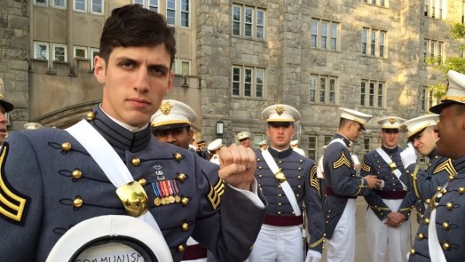 "Second Lt. Spenser Rapone is seen in an undated photo making a fist and holding a cap with a sign inside that reads, ""Communism will win."" (Twitter)"