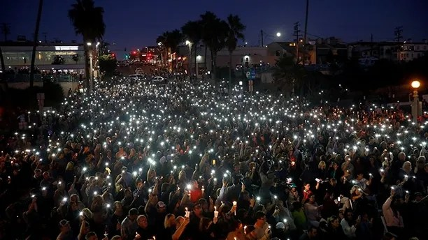 People hold candles and flashlights into the air during a memorial for Rachael Parker and Sandy Casey, Manhattan Beach city employees and victims of the October 1st Las Vegas Route 91 music festival mass shooting, in Manhattan Beach, California, U.S., October 4, 2017.  REUTERS/Patrick T. Fallon - RC14CD4E6E10