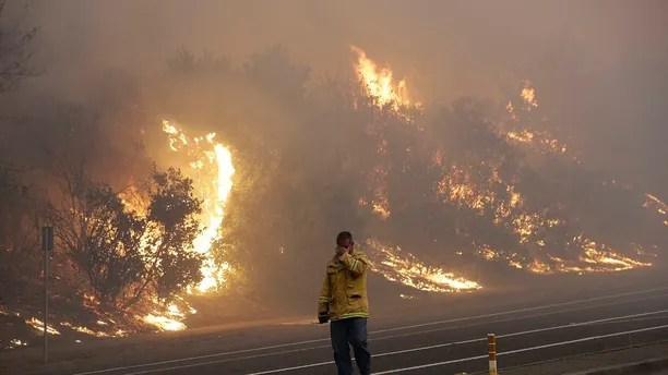 A firefighter covers his eyes as he walks past a burning hillside in Santa Rosa, Calif., Monday, Oct. 9, 2017. Wildfires whipped by powerful winds swept through Northern California, sending residents on a headlong flight to safety through smoke and flames as homes burned. (AP Photo/Jeff Chiu)