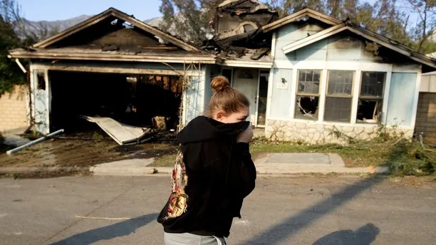 Carrie Shore walks by her neighbors wildfire damaged home along Via San Anselmo in the Sylmar area of Los Angeles Wednesday, Dec. 6, 2017. (AP Photo/Chris Carlson)