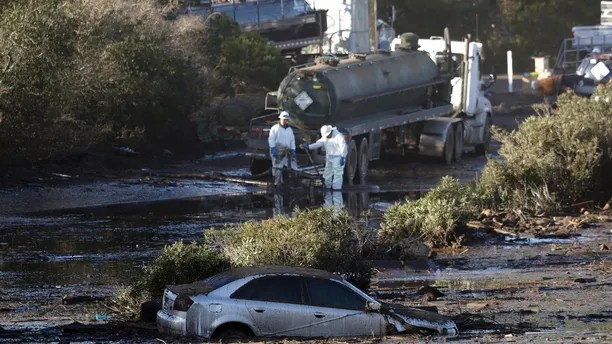 Crews pump mud on Highway 101 after a mudslide Saturday, Jan. 13, 2018, in Montecito, Calif.  Most of the people of Montecito, a town usually known for its serenity and luxury, were under orders to stay out of town as gas and power were expected to be shut off Saturday for repairs. (AP Photo/Marcio Jose Sanchez)