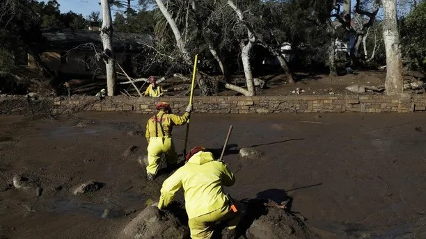 A Cal Fire search and rescue crew walks through mud near homes damaged by storms in Montecito, Calif., Friday, Jan. 12, 2018.  The mudslide, touched off by heavy rain, took many homeowners by surprise early Tuesday, despite warnings issued days in advance that mudslides were possible because recent wildfires had stripped hillsides of vegetation that normally holds soil in place.