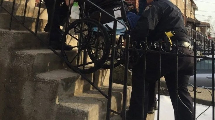 NYPD Officers Vitaliy Zelikov and Georin Duran work together to carry a wheelchair-bound 85-year-old man up the stairs.