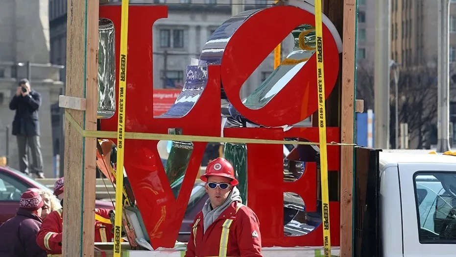 """LOVE"", the famous 1976 Robert Indiana sculpture, is parked in front of John F. Kennedy Plaza before reinstallation, Tuesday Feb. 13, 2018 in Philadelphia. The sculpture was removed for repairs a year ago while its home, the downtown park, was going through a renovation. (AP Photo/Jacqueline Larma)"