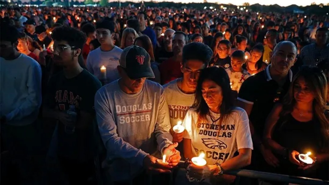 Jorge Zapata, Jr., center, a student at Marjory Stoneman Douglas High School, holds candles with his mother Lavinia Zapata, and father Jorge Zapata, Sr., during a candlelight vigil for the victims of the Wednesday shooting at the school, in Parkland, Fla., Thursday, Feb. 15, 2018. Nikolas Cruz, a former student, was charged with 17 counts of premeditated murder on Thursday. (AP Photo/Gerald Herbert)